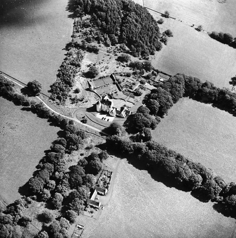 Oblique aerial view centred on the country house with the stables adjacent, taken from the WNW.
