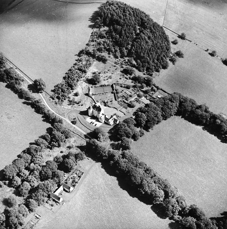 Oblique aerial view centred on the country house with the stables adjacent, taken from the W.
