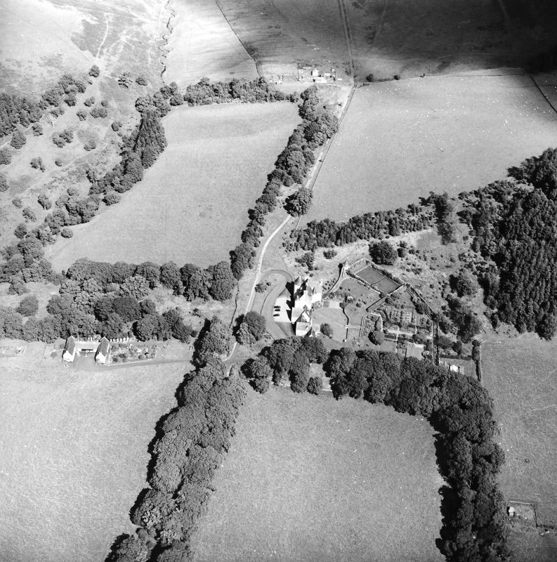 Oblique aerial view centred on the country house with the stables adjacent, taken from the SW.
