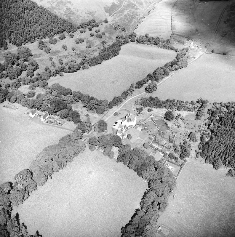 Oblique aerial view centred on the country house with the stables adjacent, taken from the SSW.