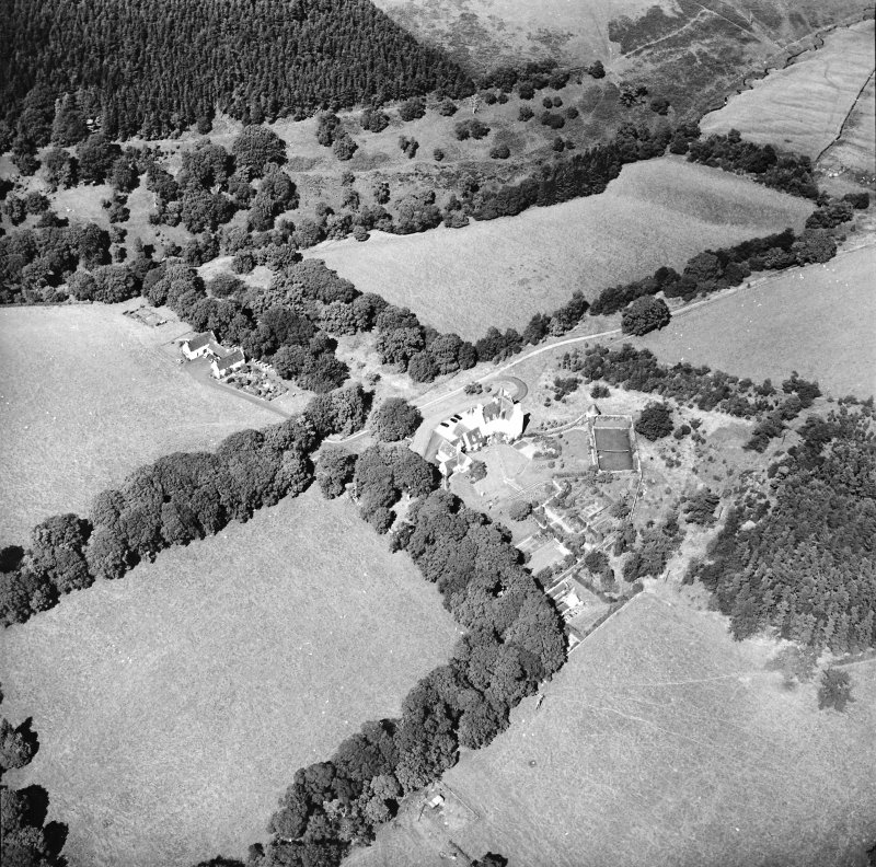 Oblique aerial view centred on the country house with the stables adjacent, taken from the S.
