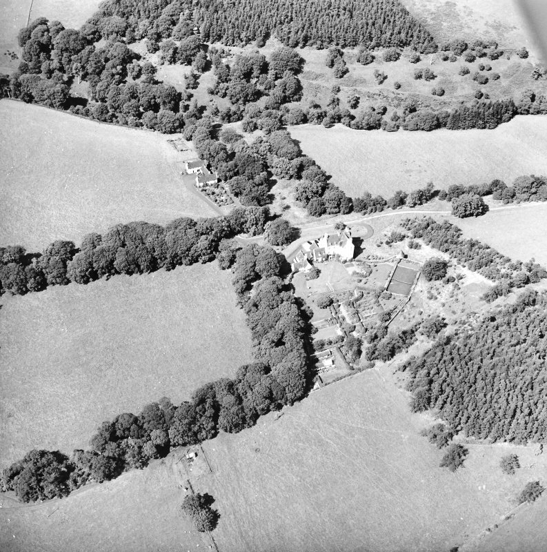 Oblique aerial view centred on the country house with the stables adjacent, taken from the SSE.