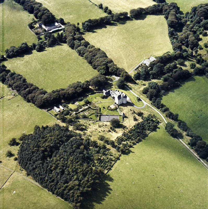 Oblique aerial view centred on the country house with the stables and farmsteading adjacent, taken from the E.