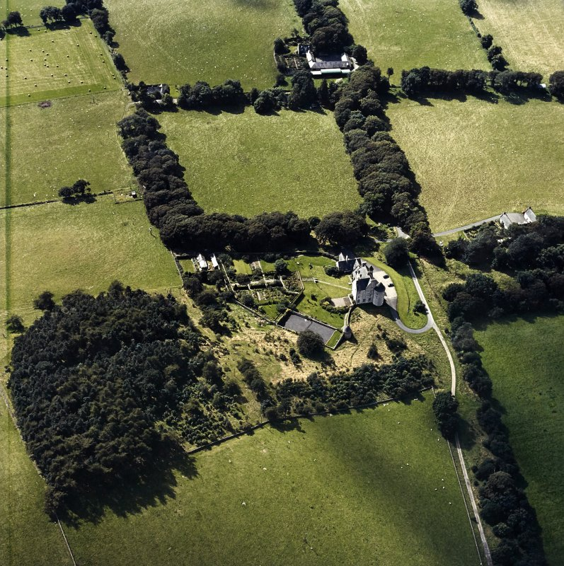 Oblique aerial view centred on the country house with the stables and farmsteading adjacent, taken from the ENE.