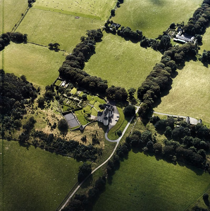 Oblique aerial view centred on the country house with the stables and farmsteading adjacent, taken from the NNE.