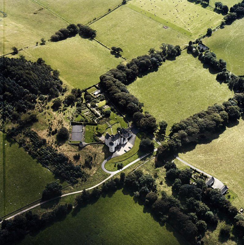 Oblique aerial view centred on the country house with the stables adjacent, taken from the N.