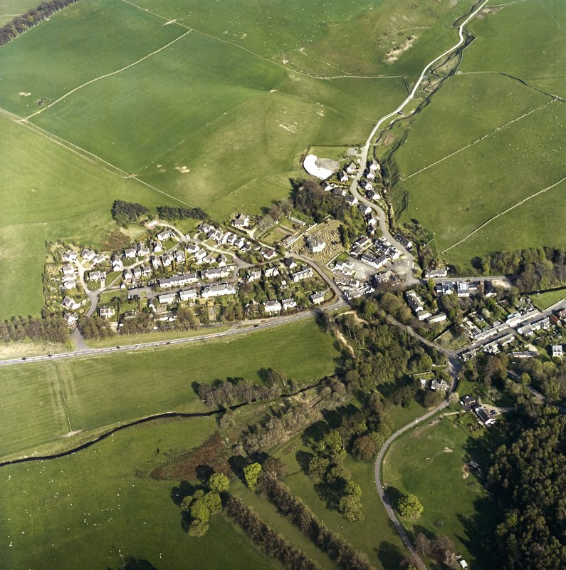 Oblique aerial view of Eddleston centred on the church and churchyard, taken from the WNW.