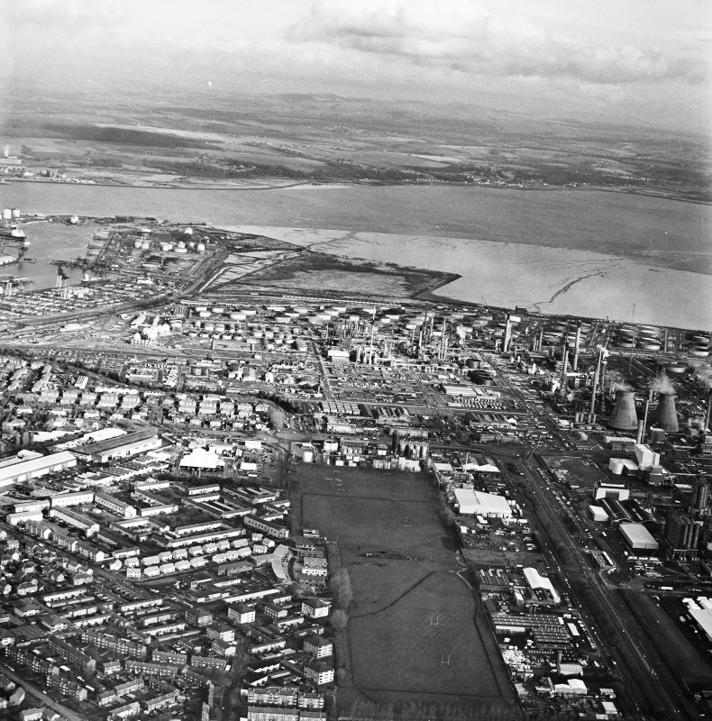 General oblique aerial view looking over the oil refinery across the River Forth towards Fife, taken from the W.