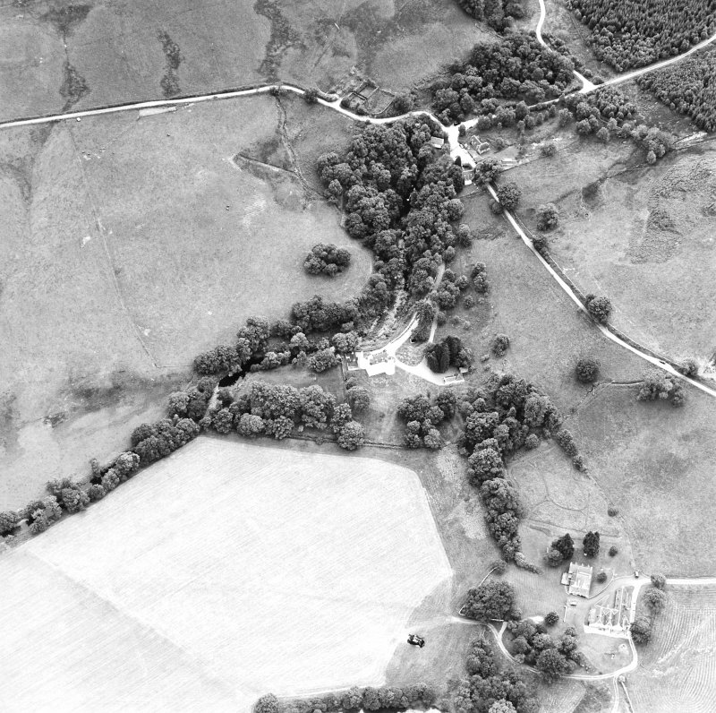 Oblique aerial view centred on the castle with farmstead adjacent, taken from the NNW.