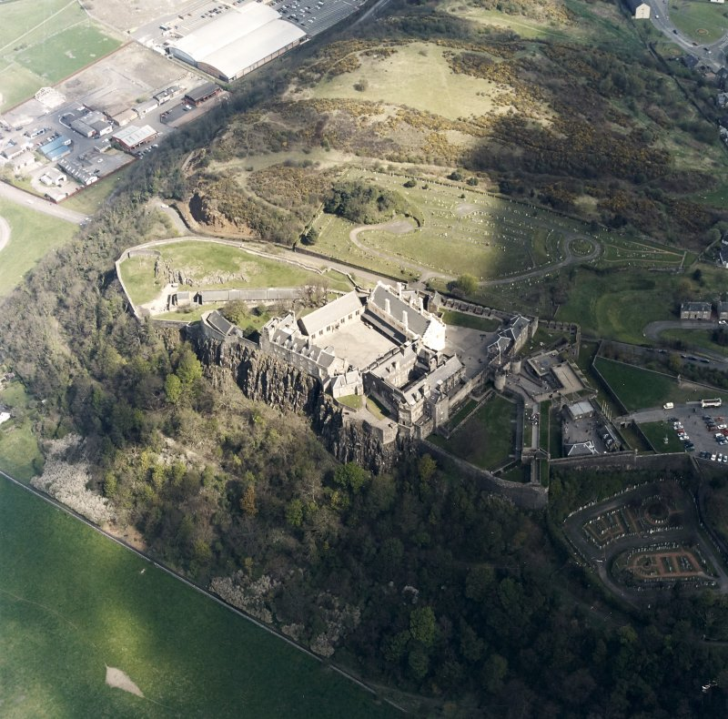Oblique aerial view centred on the castle with the cemetery adjacent, taken from the SSW.