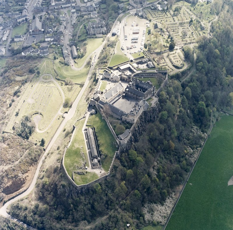 Oblique aerial view centred on the castle with the cemetery and burial-ground adjacent, taken from the NW.