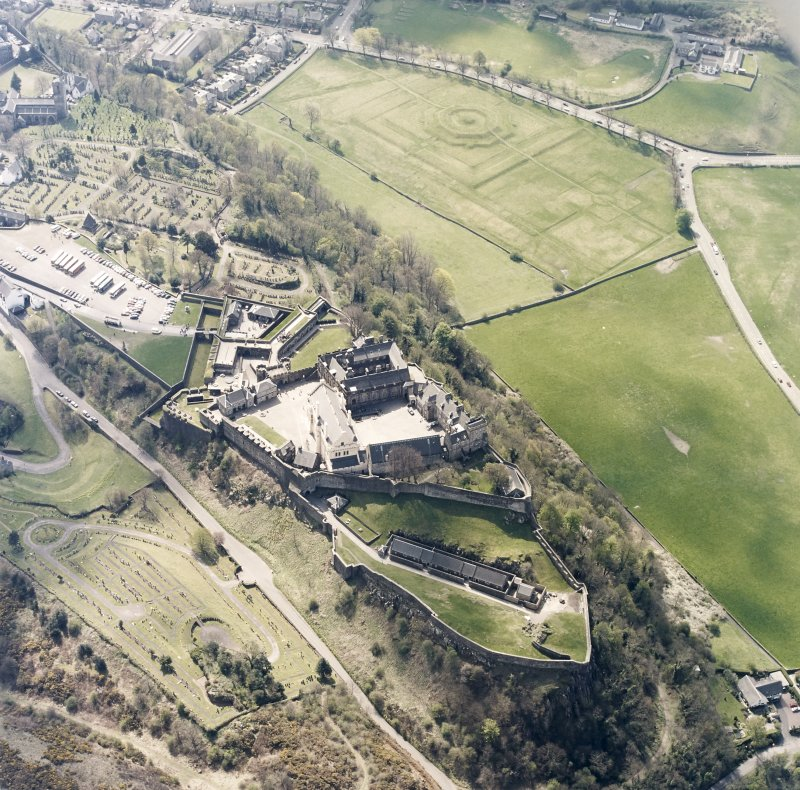 Oblique aerial view centred on the castle with the garden and burial-ground adjacent, taken from the N.