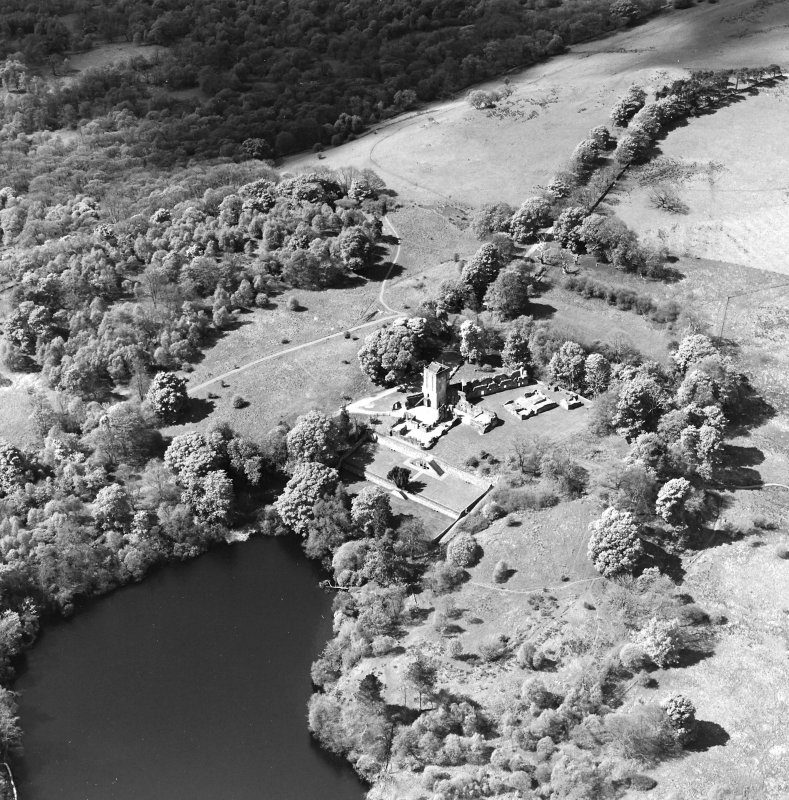 Oblique aerial view centred on the remains of the castle and tower, taken from the ENE.