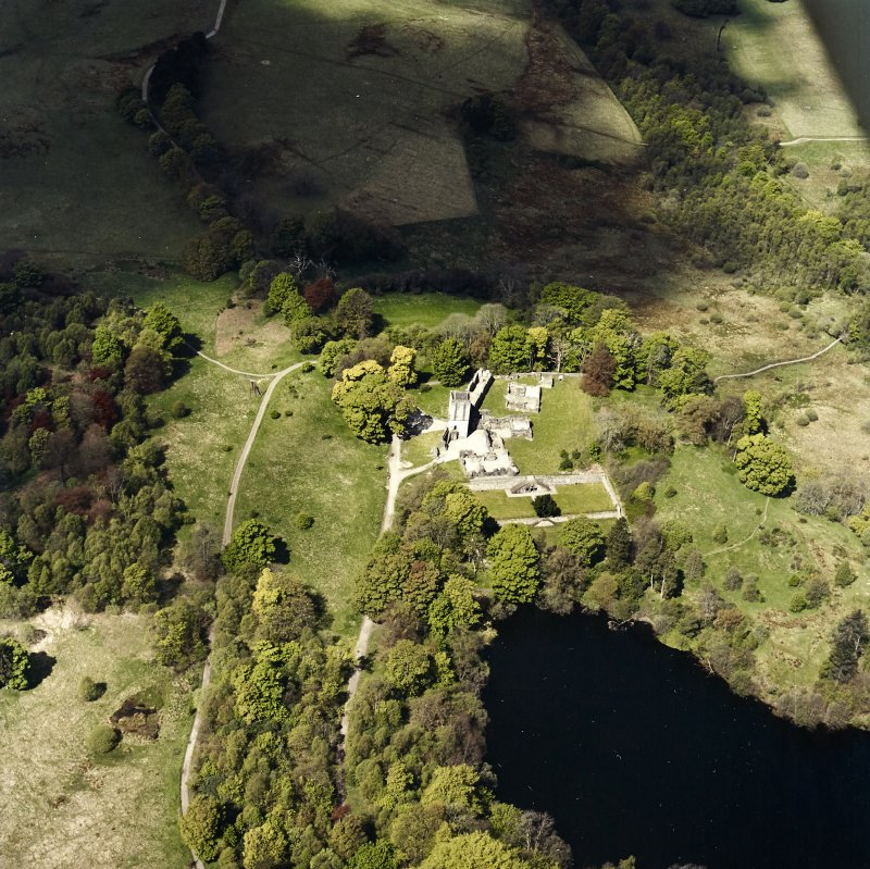 Oblique aerial view centred on the remains of the castle and tower, taken from the SE.