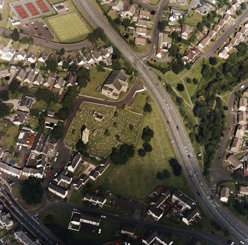 Oblique aerial view centred on the burial ground, belfry and clock tower with church and manse adjacent, taken from the SW.