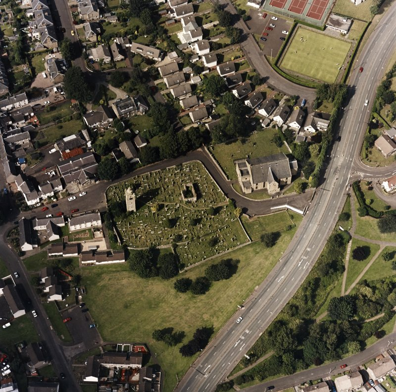 Oblique aerial view centred on the burial ground, belfry and clock tower with church and manse adjacent, taken from the S.
