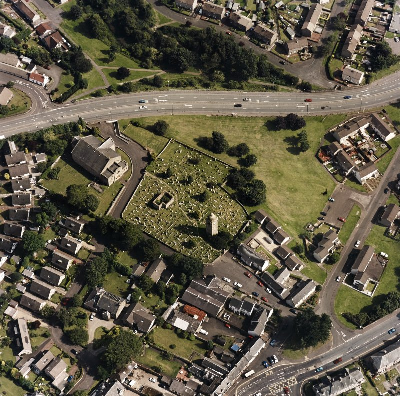 Oblique aerial view centred on the burial ground, belfry and clock tower with church and manse adjacent, taken from the NW.
