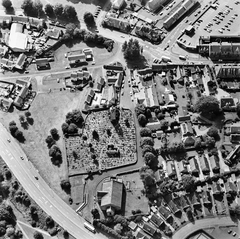 Oblique aerial view centred on the burial ground, belfry and clock tower with church and manse adjacent, taken from the ENE.