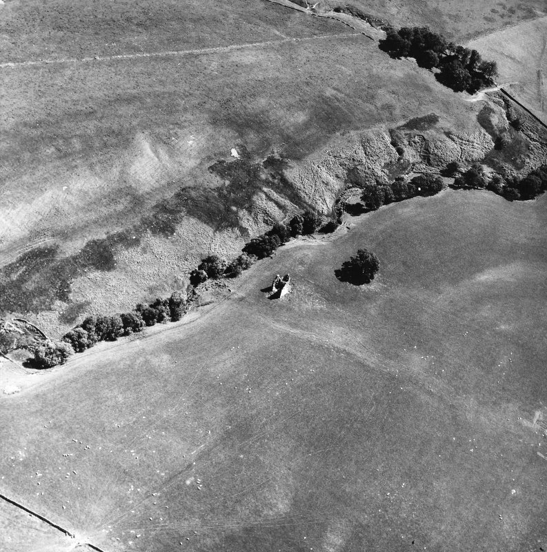 Oblique aerial view centred on tower house from NW.