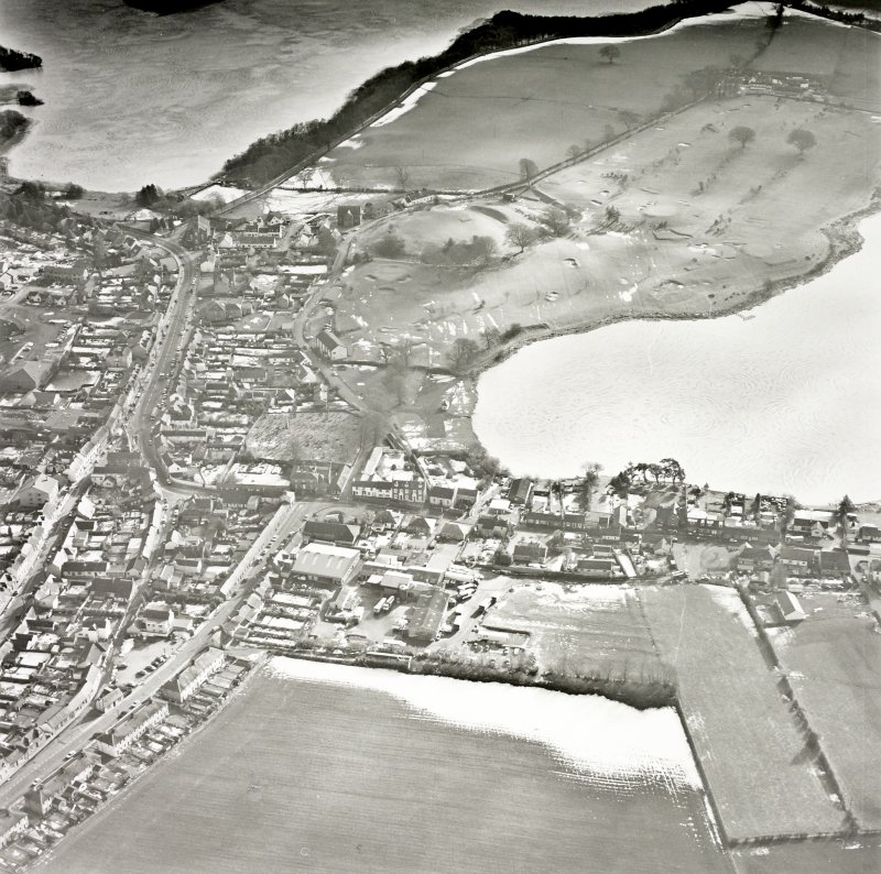 Oblique aerial view, taken from the NNW, centred on the S part of the town, with St Mary Magdalene's church and burial ground and Lochmaben old castle and motte visible in the centre of the photograph.