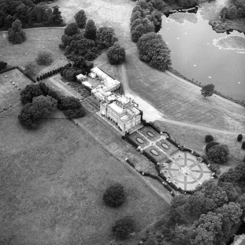 Oblique aerial view centred on country house from SE.