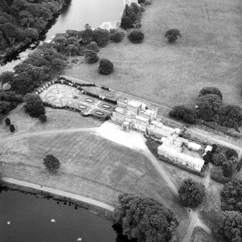 Oblique aerial view centred on country house from NW.