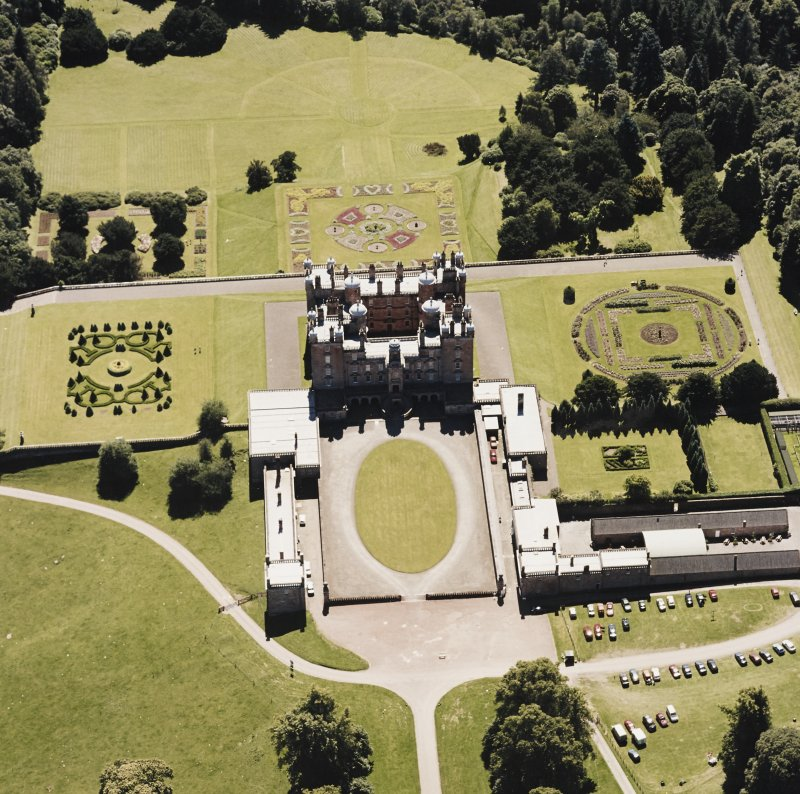 Oblique aerial view centred on the country house, garden, coach house and stables, taken  from the NNE.