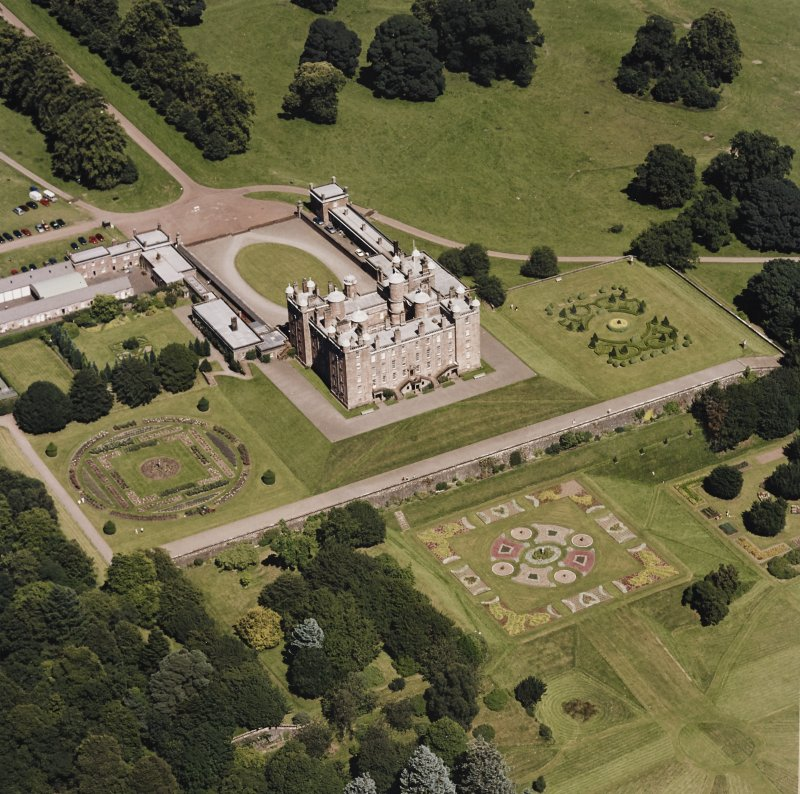 Oblique aerial view centred on the country house, garden, coach house and stables, taken  from the SW.
