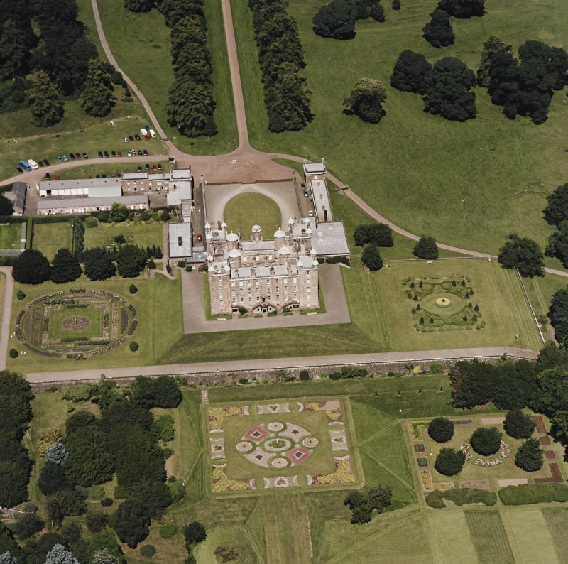 Oblique aerial view centred on the country house, garden, coach house and stables, taken  from the SSW.