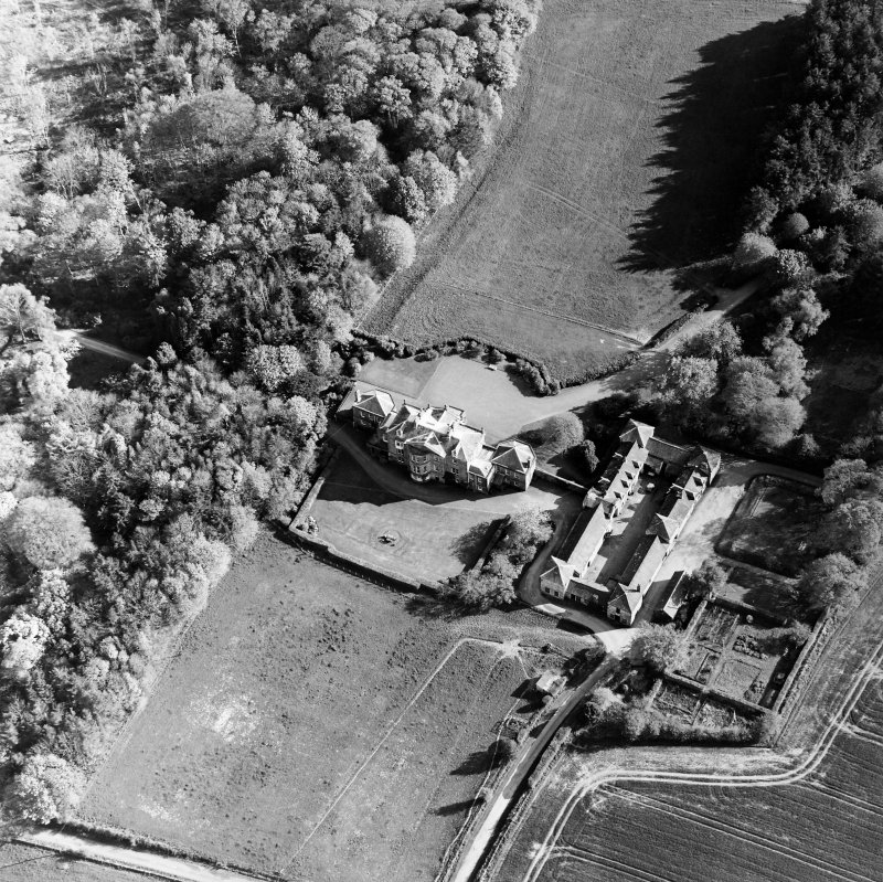 Oblique aerial view centred on the country house and stables, taken from the NNE.