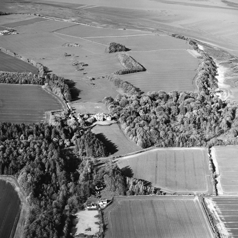 General oblique aerial view looking over cottage, country house, stables and gardens towards Tallowquhairn, taken from the SW.