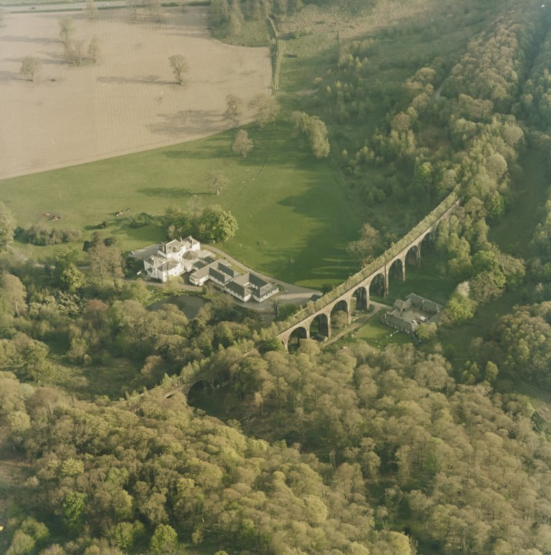 Oblique aerial view centred on the country house, railway viaduct and stables, taken from the NNW.