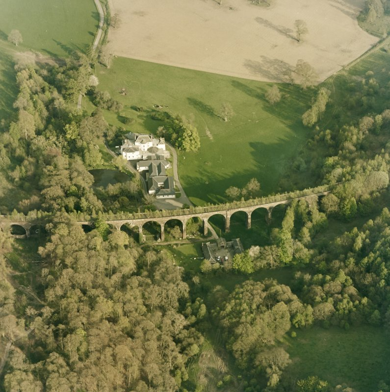 Oblique aerial view centred on the country house, railway viaduct and stables, taken from the NW.