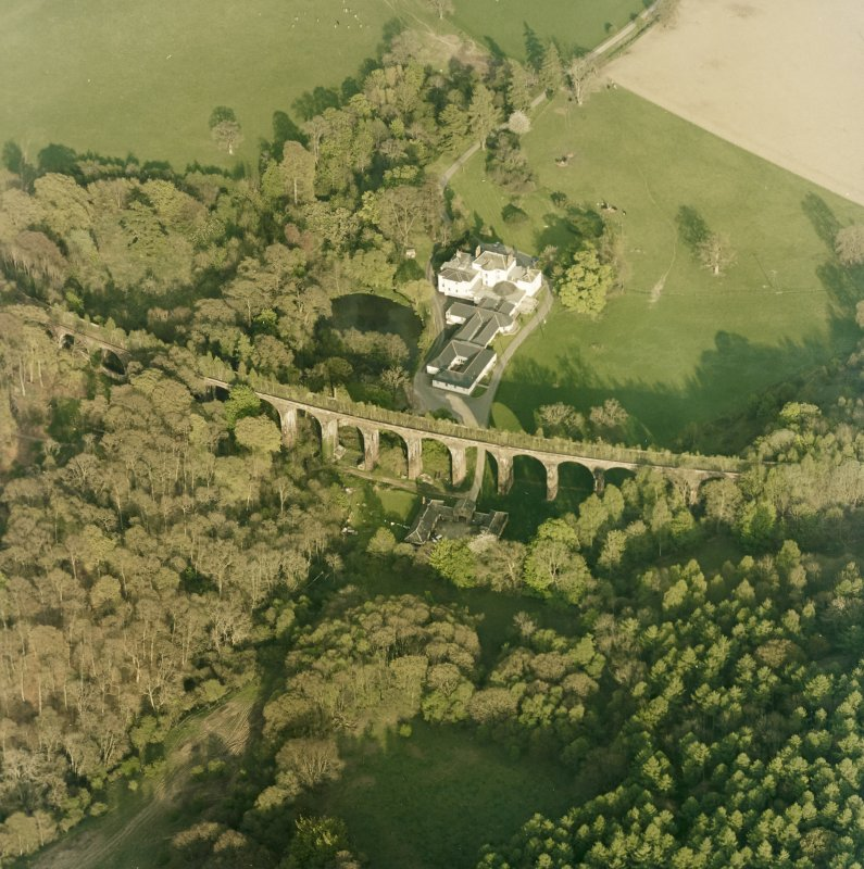 Oblique aerial view centred on the country house, railway viaduct and stables, taken from the WNW.