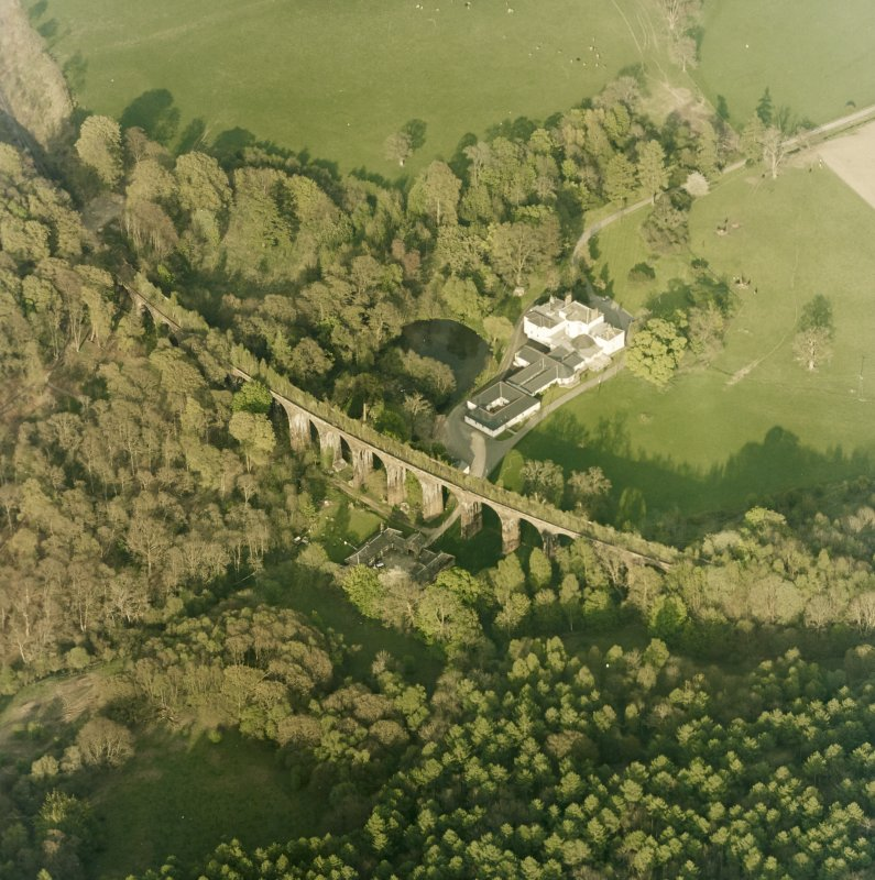 Oblique aerial view centred on the country house, railway viaduct and stables, taken from the W.