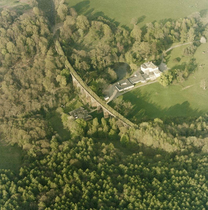 Oblique aerial view centred on the country house, railway viaduct and stables, taken from the WSW.
