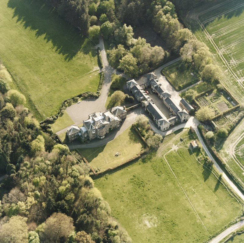 Oblique aerial view centred on the country house and stables, taken from the NE.