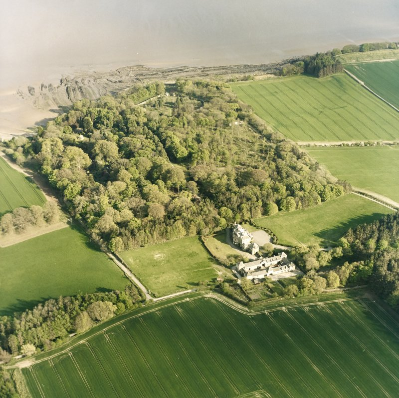Oblique aerial view centred on the country house, stables, gardens and walled garden, taken from the NW.