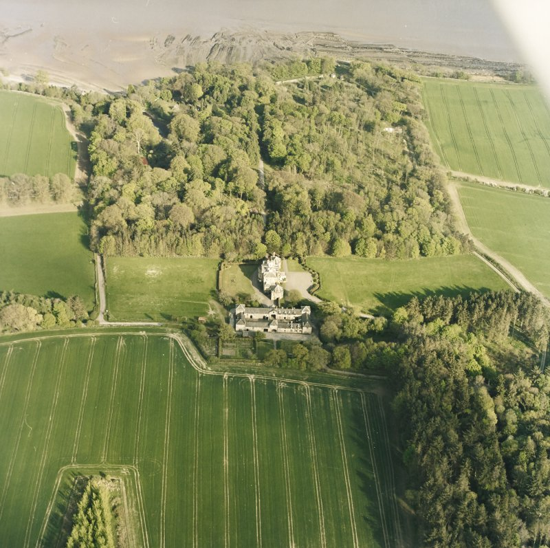 Oblique aerial view centred on the country house, stables, gardens and walled garden, taken from the WNW.