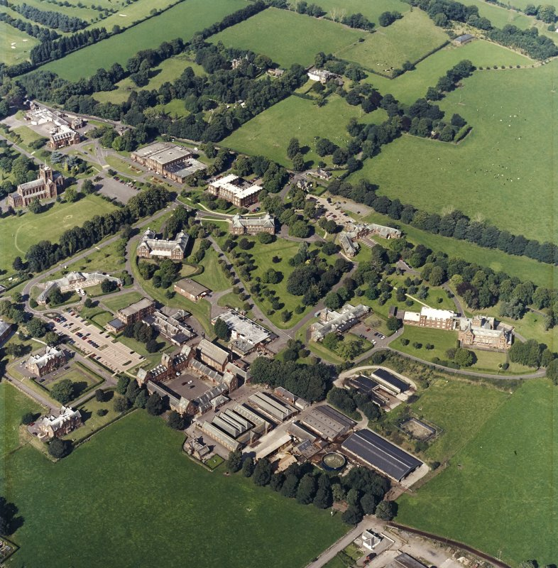 Oblique aerial view centred on the hospital and the church, taken from the SSW.