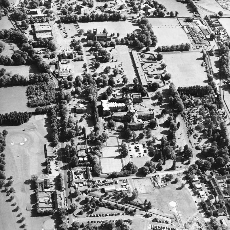 Oblique aerial view centred on the hospital and the church, taken from the NNW.