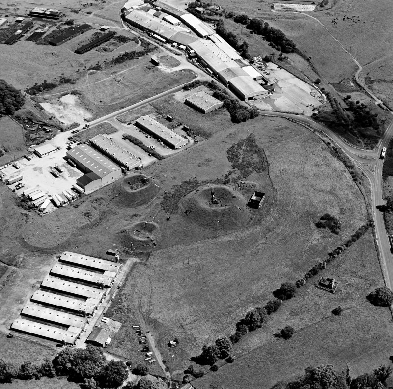 Oblique aerial view centred on Unit 2 of the explosives works and armament depot, showing the earthworks for the charge houses with in the background the S canteen and loading banks. taken from the NW. Also visible is Edingham Castle, Edingham Industrial Estate with Edingham farm poultry houses.