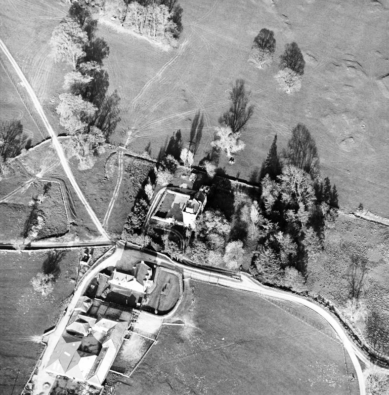 Oblique aerial view centred on the tower-house with farmsteading adjacent, taken from the WSW.