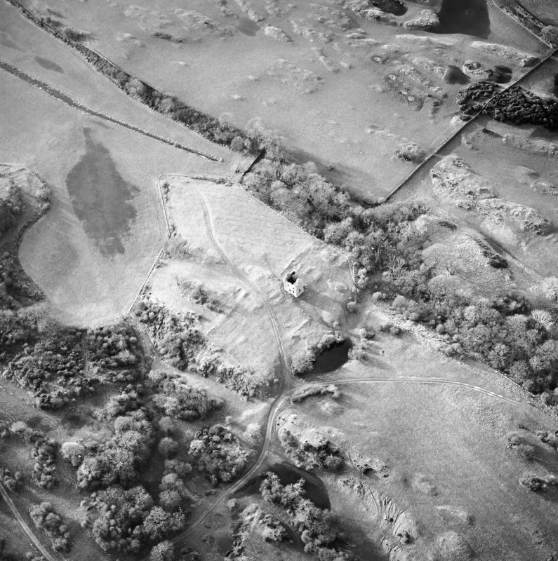 Oblique aerial view centred on the remains of the tower-house, possible garden, buildings and rig, taken from the ENE.
