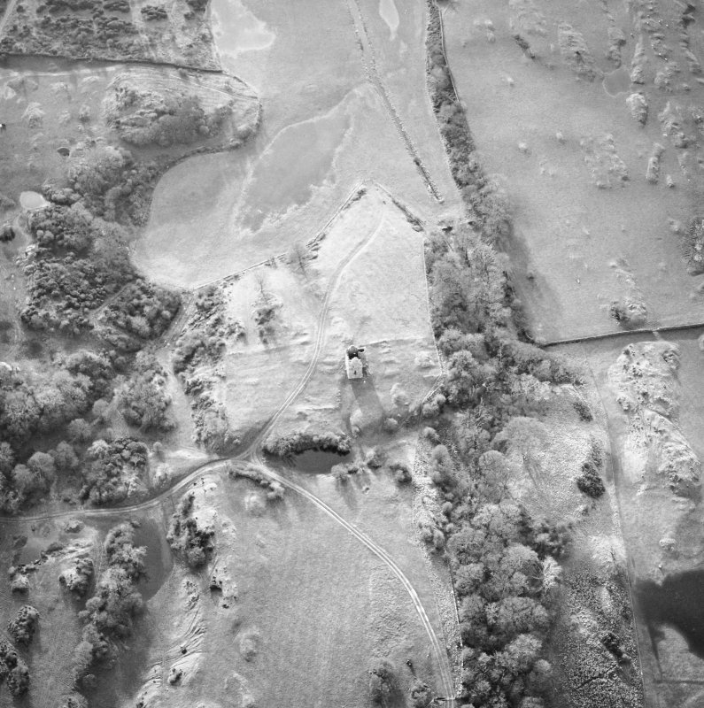 Oblique aerial view centred on the remains of the tower-house, possible garden, buildings and rig, taken from the NE.