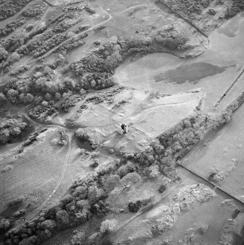 Oblique aerial view centred on the remains of the tower-house, possible garden, buildings and rig, taken from the N.