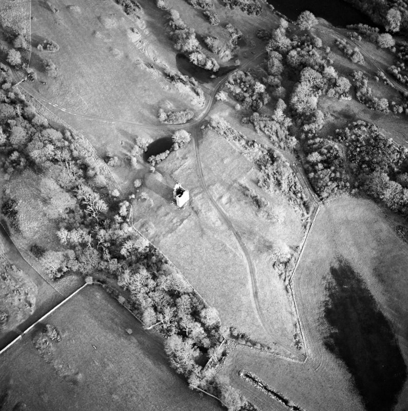 Oblique aerial view centred on the remains of the tower-house, possible garden, buildings and rig, taken from the WSW.