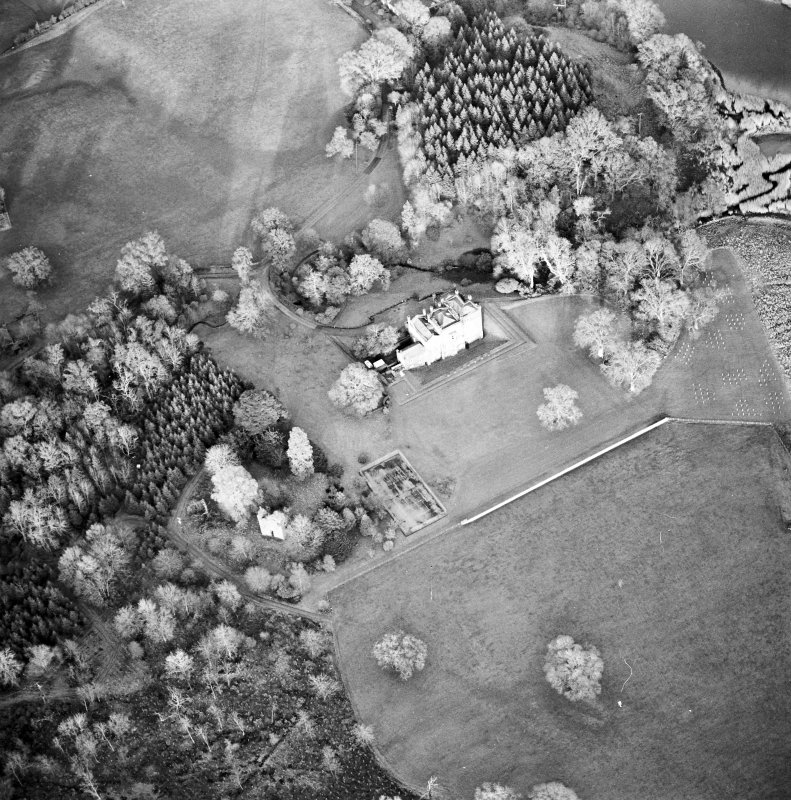 Oblique aerial view centred on the country house with tower-house and garden adjacent, taken from the SW.