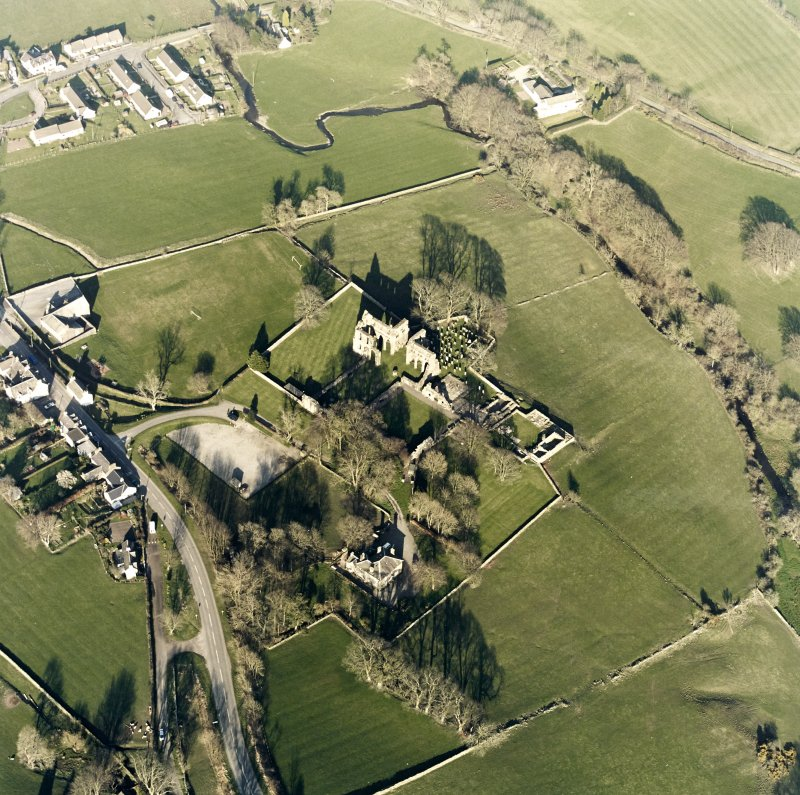 Oblique aerial view centred on the abbey and manse, taken from the SW.