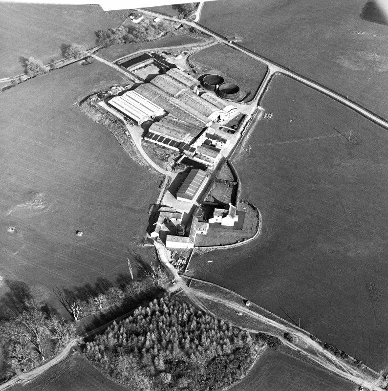 Oblique aerial view centred on the farmstead with the site of the well adjacent, taken from the W